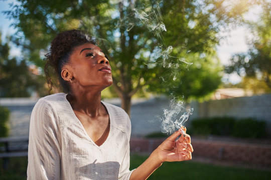 happy african american woman smoking marijuana joint in back yard