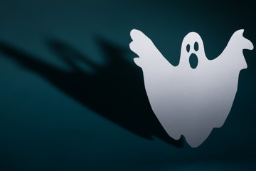 Halloween background concept. Funny ghost doing boo gesture and graphic shade behind on dark blue table.