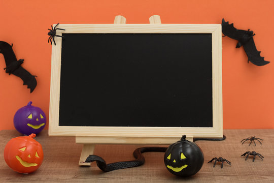 Halloween background concept. Front view of blackboard with decoration objects, pumpkin, bats, snake, spiders on orange backdrop