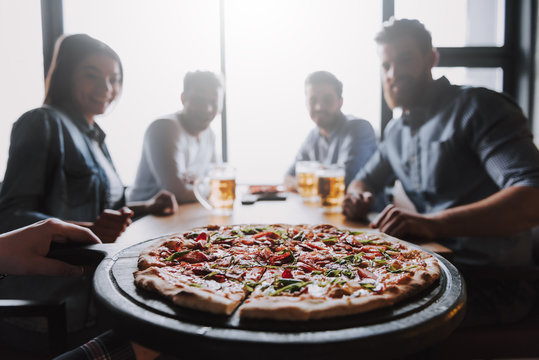 Close Up of Pizza on Table with Company Friends
