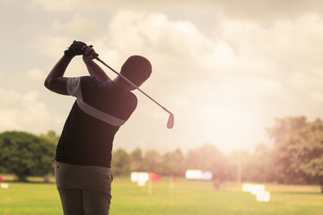Foto op Plexiglas Golf Man hitting golf shot with club on course at evening time.