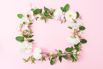 Frame of white flowers and leaves on pink pastel background. Flat lay, top view. Copy space