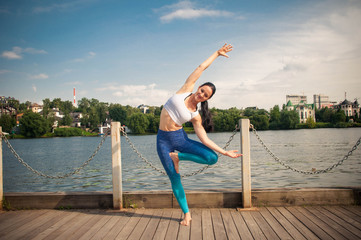 Young pretty fit and slim woman practices yoga and meditation on the embankment of the river