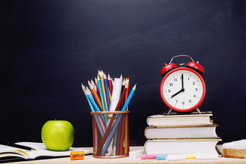 Stationery Supplies and accessories, Alarm Clock, Color Chalk,eraser,Crayon, Pencil,sharpener,pen, apple green, book, put on the desk Stationery Blackboard Background. Education back to school concept