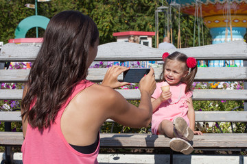 Mom takes pictures of her daughter in the park on a smartphone