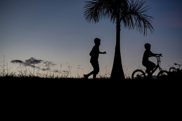 Silhouette of a boy walking, another boy on a bicycle - outdoors