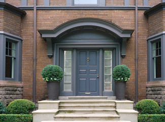 elegant front door with shrubbery