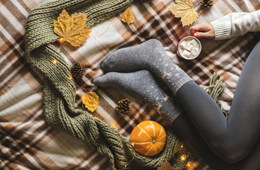 Women's hands and feet in sweater and woolen cozy gray socks holding cup of hot coffee with marshmallow, sitting on plaid with pumpkin, knitted scarf, leaves. Concept winter comfort, morning drinking.