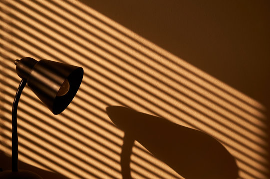 Morning sunlight coming through the window through venetian and sun-lighting a lamp and creating sunlit lamp & venetian shadow on the wall.
