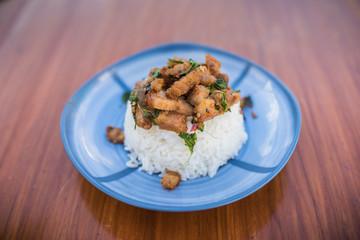 Thai food, Khao Kaprao Hmoo Krob, crispy pork fried with sweet brasil cover the steam rice