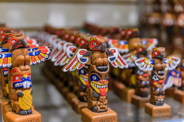 Carved wooden miniature First Nations or Native American Indian totem pole souvenirs at a tourist shop in Vancouver Canada