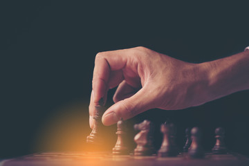 Retro style image of a businessman with clasped hands planning strategy with chess figures on an old wooden table.
