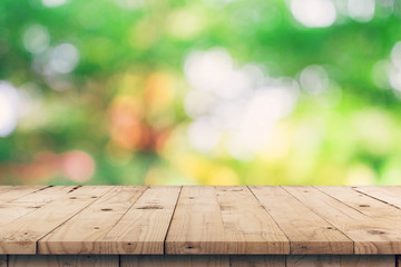 Empty wooden table top and green bokeh display montage for product with space. Wall mural