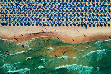 Aerial top view on the beach. Umbrellas, sand and sea waves