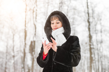 Technology, people and winter concept - Young woman with smartphone and winter landscape snowflakes on the background