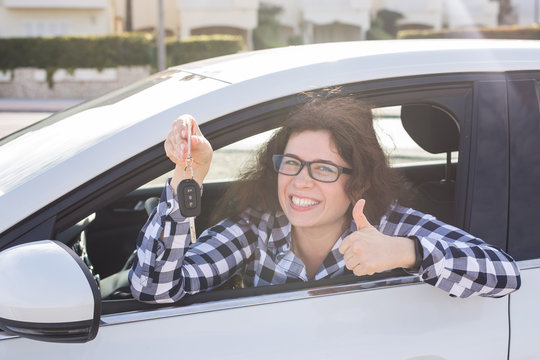 Happy woman showing thumb up and driving a new car. Positive face expression
