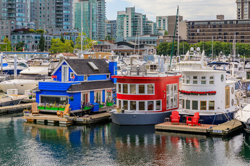 Houseboats docked in the marina at the Coal Harbour waterfront in Vancouver Canada