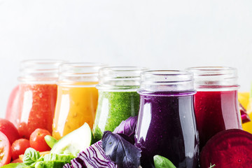 Multicolored vegan vegetable juices and smoothies in glass bottles on gray table, selective focus
