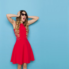 Bautiful Woman In Red Dress And Sunglasses Is Holding Head In Hands And Shouting