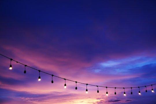 light bulb decor on string sunset sky on the beach