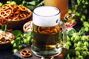 Light german beer poured into big glass, fresh green hops and bowls with salty snacks and nuts, autumn beer festival concept, dark background, selective focus