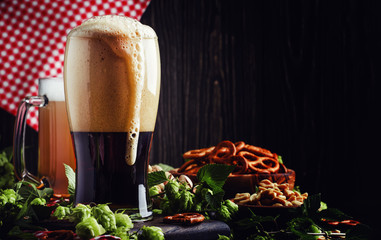 Dark German beer is poured into a glass, fresh green hops and bowls with salty snacks and nuts, autumn beer festival concept, dark background, selective focus