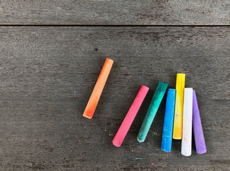 Chalk sticks pastel multi color (purple,blue,green,red,orange,yellow,white) on wood table background