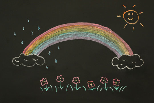 Actual drawing on black chalk board. Colorful rainbow on clouds with sun shining it's light,  some raindrops and red flowers with little green leaves blooming.