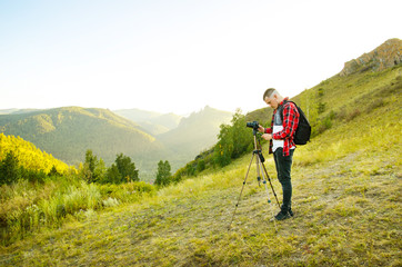 Young guy photographer takes pictures of nature with mountains on a SLR camera.