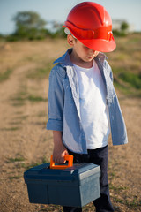 tired upset little boy worker in helmet with toolbox in hand outdoors jobless