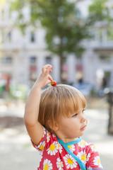 Child holding fresh strawberry in hand. Kind hält frische Erdbeere in Hand.