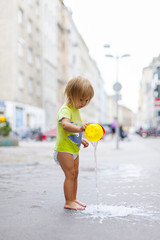 Kleines Kind spielt Barfuß in Stadt mit Wasser. Little child playing barefoot with water in city street.