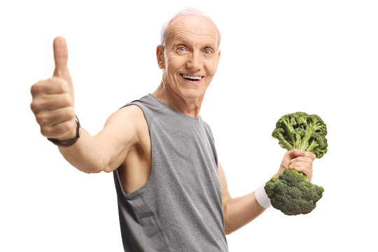 Senior man holding a broccoli dumbbell and showing thumbs up