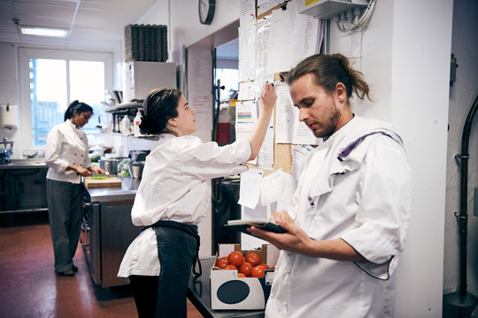 Female chef making checklist while colleagues working in kitchen