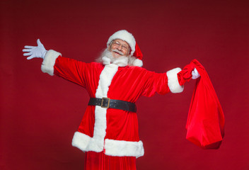 Christmas. Kind smiling Santa Claus spread his hands to the sides. In one hand he is holding a red bag with gifts. Isolated on red background.