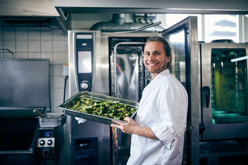 Portrait of confident chef with broccoli in baking sheet at commercial kitchen