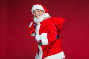Christmas. Kind and tired Santa Claus in white gloves carries a red bag with gifts over his shoulder. Isolated on red background.