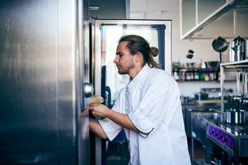 Male chef putting bread in oven at commercial kitchen
