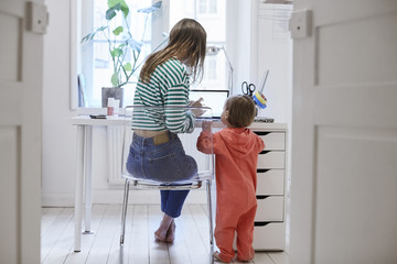 Rear view of girl standing by mother using laptop at table