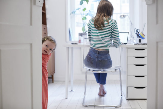 Girl standing behind door while mother working on laptop in background at home