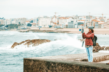 Young beautiful traveler girl with a backpack taking off the ocean and waves on a smartphone, winter, Atlantic ocean, Portugal