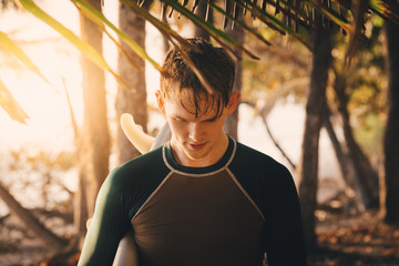 Young male surfer at beach during sunset