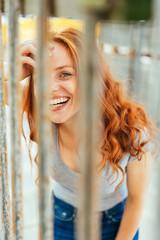 Laughing happy woman peering through iron bars