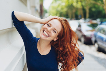 Happy friendly young woman leaning on a building