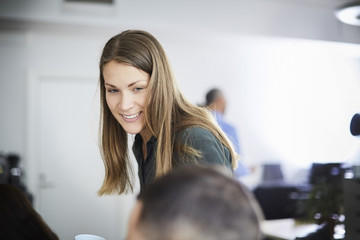 Smiling businesswoman looking at coworker in office