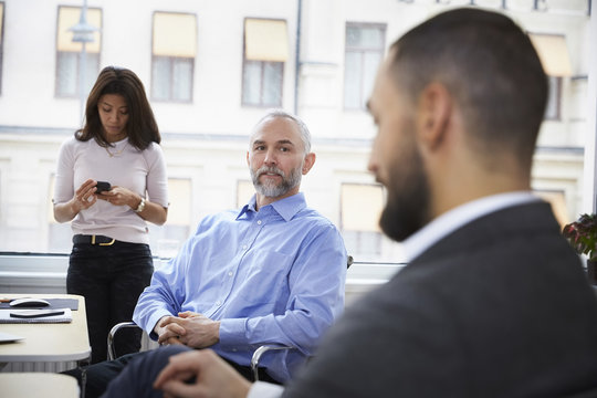 Mature businessman explaining with colleague in meeting at office