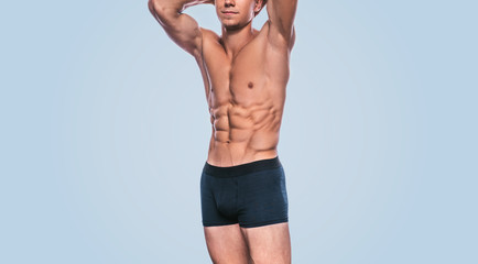 Attractive fitness male model in black underwear showing his abdominal torso on a blue background. Image of sporty handsome strong athletic man with sexy abdomen posing in studio. Healthy lifestyle