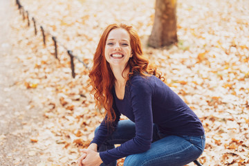 Cute young redhead woman sitting in an autumn park