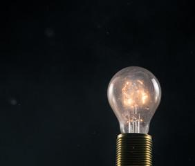 Burning old light bulb on black backround
