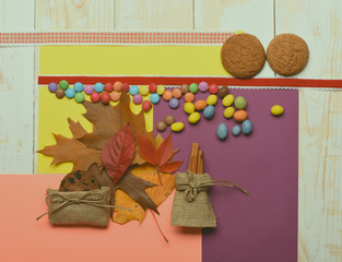Brown leaves and colorful dragee, top view. Autumn colours concept.